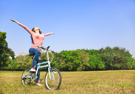 young woman relaxing pose and sitting on bike  Stock Photo