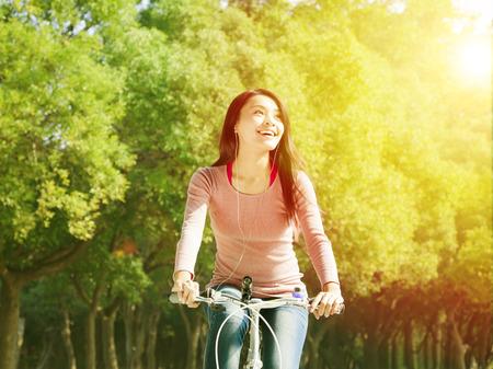 bicicleta: Mujer joven bastante asiática que monta en bicicleta en el parque Foto de archivo
