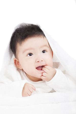 smiling baby sucking  finger under  blanket or towel  photo