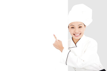Asian smiling  young woman chef pointing  with blank board photo