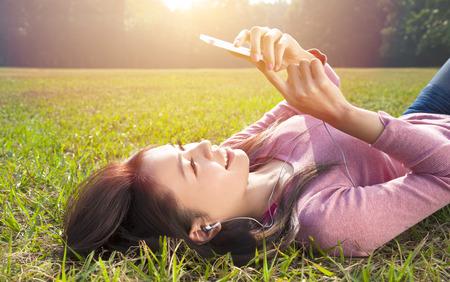 mujer joven y sonriente teléfono celular conmovedor y tumbado en la pradera