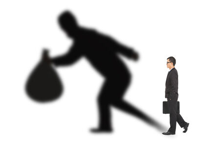 businessman walking and holding bag  with thief shadow photo
