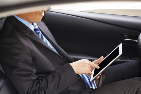 businessman touching tablet in the car photo
