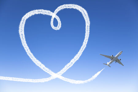 Airplane flying with the heart shape in the sky photo
