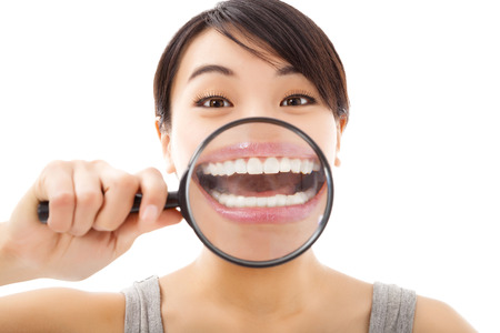 funny girl  holding magnifying to tooth photo