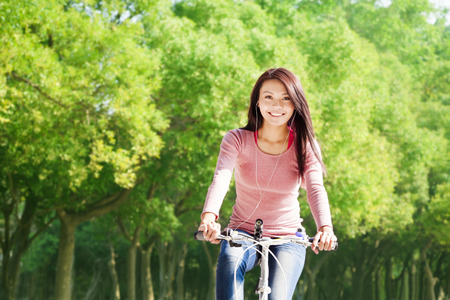 young woman riding bike and listening music in the forest Stock Photo