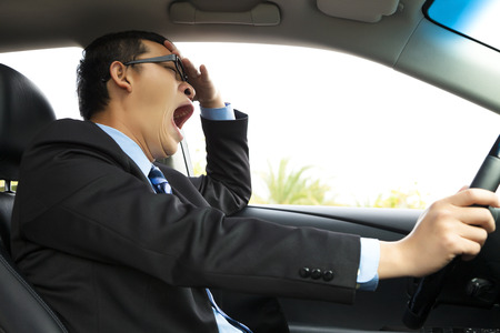 agotado: Conductor agotado el bostezo y la conducción de automóviles Foto de archivo