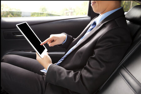 buisness: businessman working in back of car and using a tablet