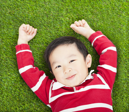 little smiling boy resting and hand up  in meadow photo