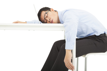 Tired overworked businessman sleeps on desk photo