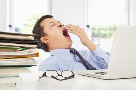 perezoso: Joven empresario agotado bostezo en el trabajo en la oficina
