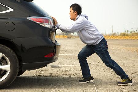 broken car: Hombre que empuja un coche roto en el camino del rock Foto de archivo
