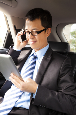 businessman working with tablet and smart phone in the car photo