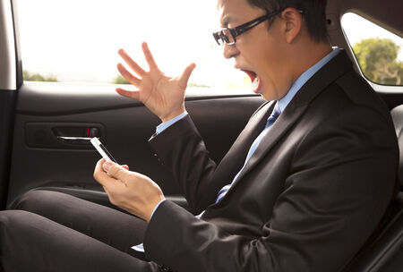 angry businessman shouting on the phone with gesture photo