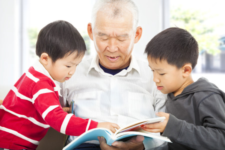 grandfather and grandchildren reading a book  photo