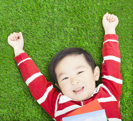 Beauty smiling child boy resting and hand up with books photo