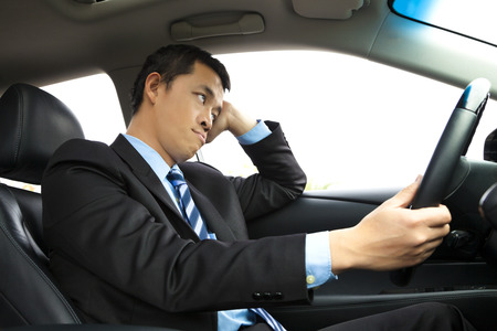 depressed businessman holding head and driving car photo