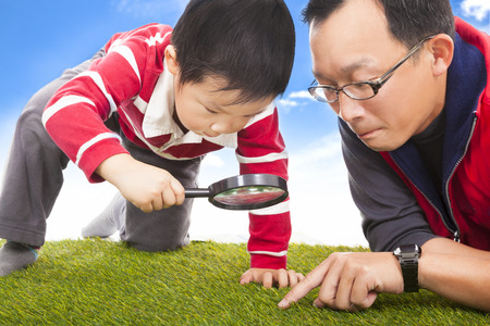 discover: father and kid with magnifying glass to discover