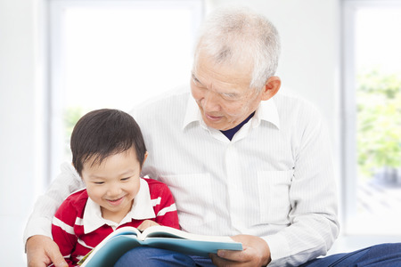 grand father reading a story book for his grandson