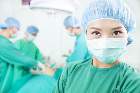 Asian Surgical woman and Surgeons  in an  operating theater photo