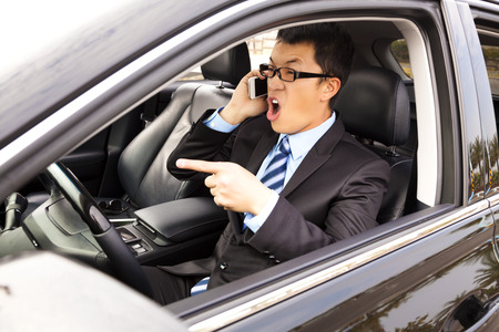 incensed: irate businessman talking with cell phone in the car