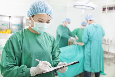 serious: asian woman Surgeons writing records on form