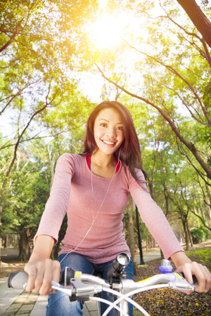 young woman riding bike and listening music on the forest trail Stock Photo - 25815472