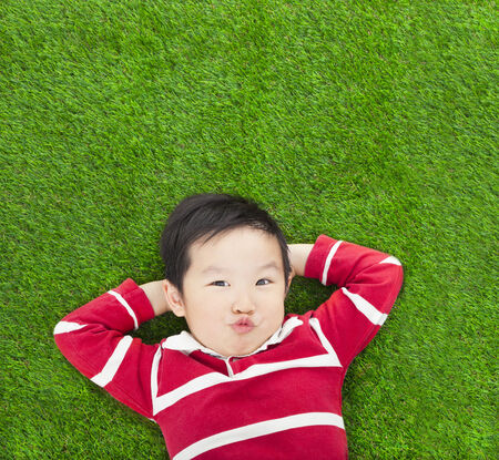 A spoof expression kid lying and holding his head photo