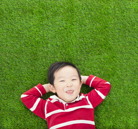 A funny kid lying and holding his head photo