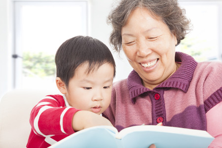 grandmother and grandson are reading story book together photo