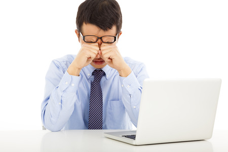 laziness: tired young businessman rubbing his eyes