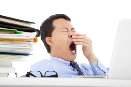 Exhausted young businessman yawning at work photo