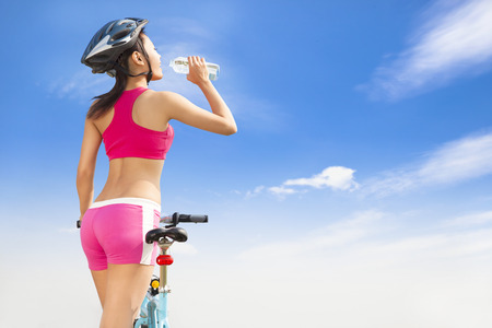 velo: Young woman drinking water with folding bike