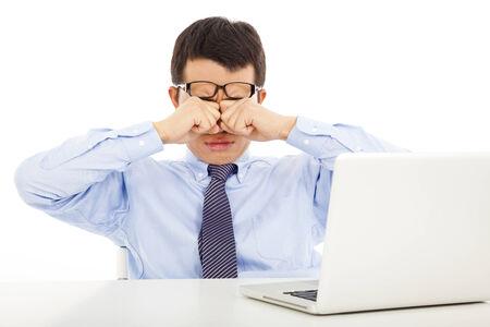 agotado: Empresario joven cansado se frotaba los ojos con el ordenador port�til Foto de archivo
