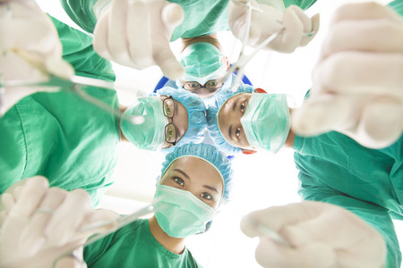Surgeons and assistant operating with surgical instruments photo