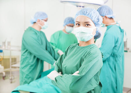 surgeon standing in front of a colleague in a surgical room photo