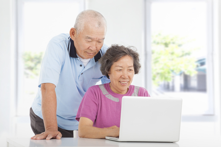 Senior couple using a laptop at home photo