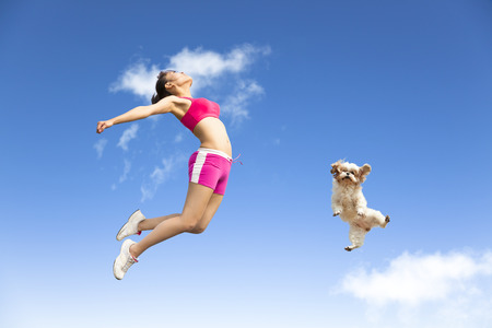 mujer joven y un perro que salta en el cielo