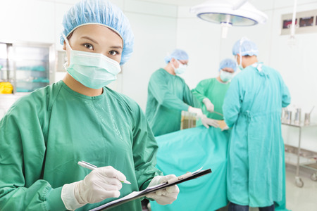 woman Surgeons writing medical record in operation room photo
