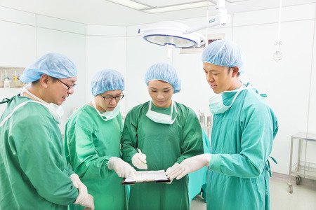 surgeons discussing about something in operating theater photo