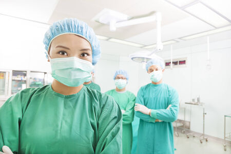 Smiling surgeon posing with a team in a surgical room Stock Photo