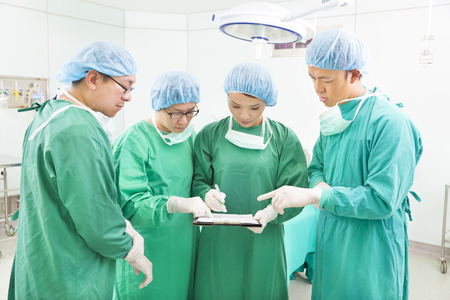 Surgeons discussing patient records in operation room photo