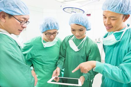 physicals: surgeons discussing with tablet in operating theater Stock Photo