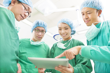 operation light: happy Surgeons discussing success operating procedure with tablet Stock Photo
