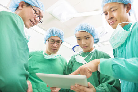 physicals: The surgeons useing  tablet  to discuss operating procedure