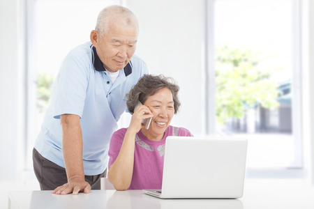 Senior couple using a laptop and a cell phone  at home photo