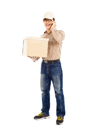 consign: delivery man talking with cell phone and holding parcel