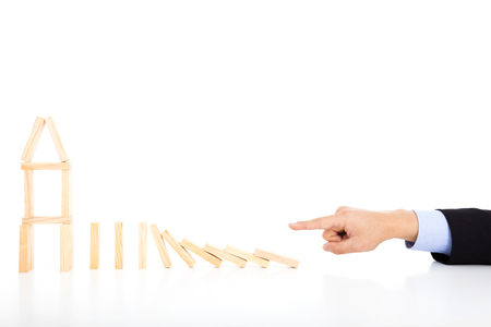 business person pushing dominoes to destroy house photo