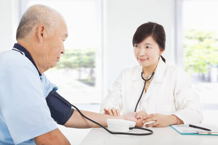 doctor measuring blood pressure of senior man at home photo