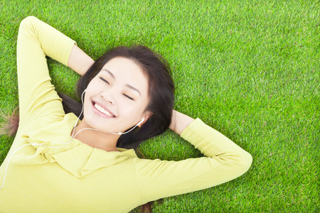 lying on grass: smiling  woman  holding head and lying  on a meadow